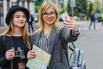 Pretty femminili turisti che prendono selfie