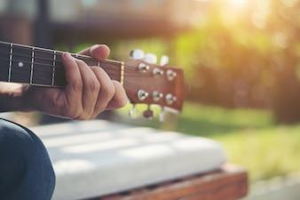 Primo piano della mano dell'uomo a suonare la chitarra acustica.