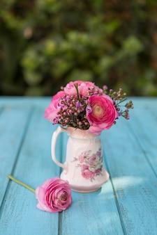 Primo piano della superficie di legno con vaso e fiori