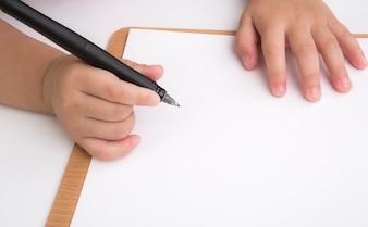 Primo piano delle mani di bambino disegno su un foglio di carta in bianco