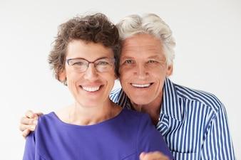 Primo piano di anziano uomo che abbraccia moglie sorridente