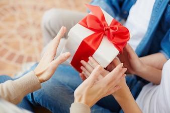 Primo piano di donna con un regalo con un fiocco rosso
