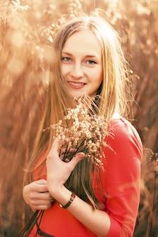 Primo piano di giovane donna con abito rosso in possesso di un mazzo di fiori