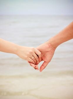 Primo piano di mani di coppia che tengono sulla spiaggia