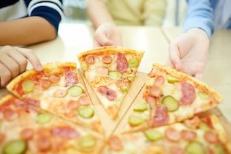 Primo piano di ragazzi afferrare pizza calda
