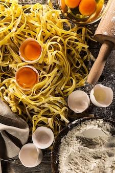 Processo di cottura di pasta con ingredienti freschi crudi per il classico cibo italiano - uova crude, farina su tavola di legno. Vista dall'alto.