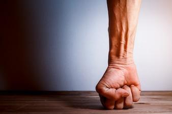 Pugno dell'uomo colpito sul pavimento di legno, Essere concetto forte