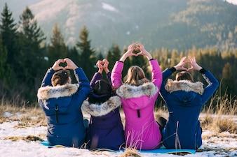 Quattro ragazze sedute nella neve, la schiena alla macchina fotografica, le mani e formano un cuore nelle montagne invernali