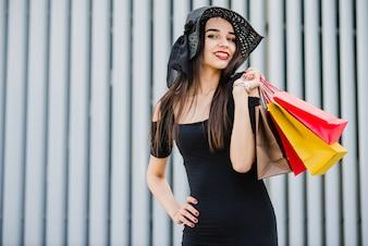 Ragazza alla moda azienda borse della spesa sorridente