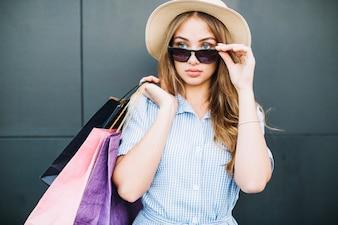 Ragazza azienda occhiali da sole dopo lo shopping