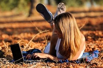 Ragazza che lavora con il suo computer portatile sdraiato a terra