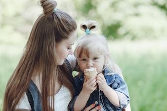 Ragazza che mangia un gelato mentre la madre la guarda e sorride