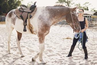 Ragazza che si prepara a cavalcare un cavallo