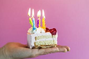 Ragazza che tiene bella torta di compleanno appetitosa con molte candele. Avvicinamento.
