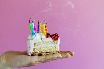Ragazza che tiene bella torta di compleanno appetitosa con molte candele sbattute. Avvicinamento.