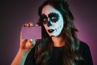 Ragazza con biglietto da visita holding makeup di halloween