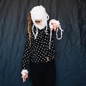 Ragazza con il volto bendato che punta il dito