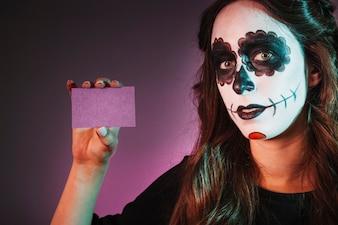 Ragazza con trucco di Halloween mostrando biglietto da visita