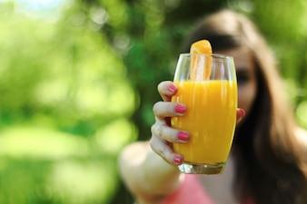 Ragazza con un bicchiere di succo di frutta