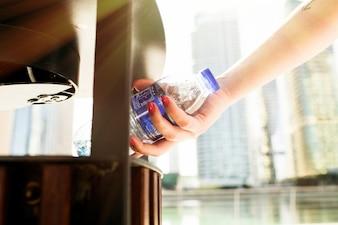 Ragazza con unghie rosse mette una bottiglia di acqua in scrapheap