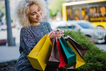 Ragazza dai capelli ricci bionda con borse per la spesa