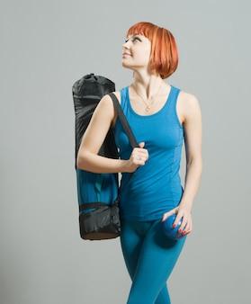 Ragazza dai capelli rossi fitness con stuoia di yoga