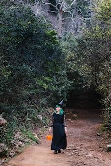 Ragazza di strega in boschi spettrali