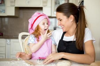 Ragazza felice leccare le dita e guardare la madre