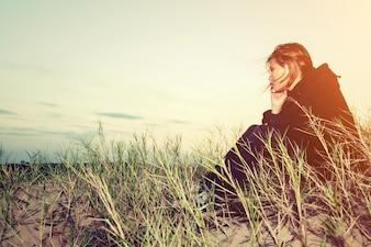 Ragazza preoccupata seduto sulla sabbia