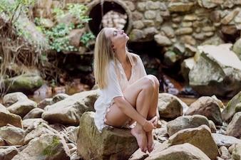 Ragazza Relaxed che si siede su una roccia all'aperto