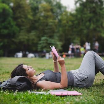 Ragazza sdraiata sull'erba nella lettura del parco