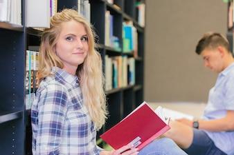Ragazza studente di college nella biblioteca