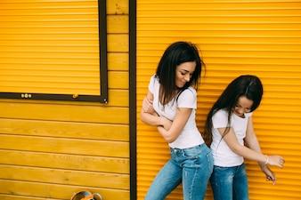 Ragazze che battono i fianchi in piedi contro il muro arancione