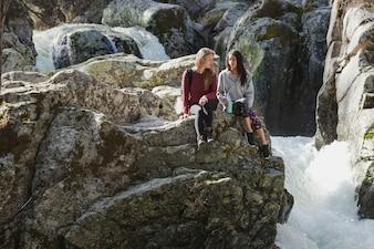 Ragazze che si siedono su una roccia e parlando