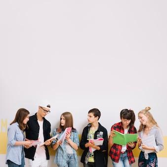 Ragazze e ragazzi che studiano al muro
