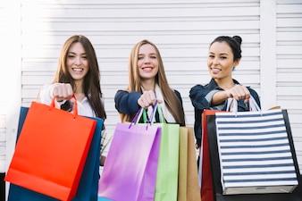 Ragazze graziose mostrando borse per la spesa
