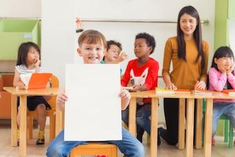 Ragazzo carino azienda manifesto bianco vuoto con felice faccia in classe scuola materna, concetto di educazione all'infanzia, foto stile stile d'epoca.