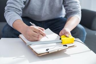 Riparazione, costruzione e casa concetto - close up di mani maschere scrivendo negli appunti