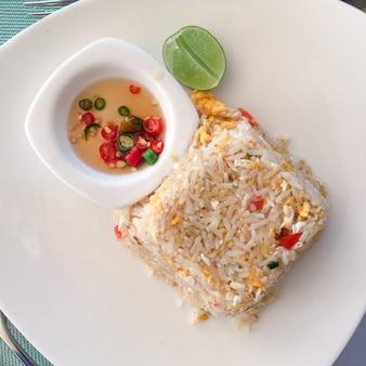 Riso fritto asiatico con uova, mais e prezzemolo close-up su un piatto, vista orizzontale dall'alto