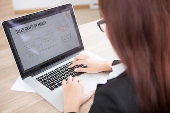 Ritagliata vista della donna di affari lavora al computer portatile