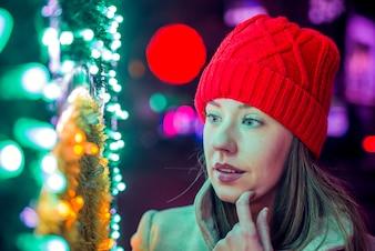 Ritratto della giovane donna nel cappello rosso lavorato a maglia. Felicità, vacanze invernali, natale e persone concetto - sorridente giovane donna in cappello rosso