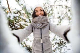 Ritratto di allegra adolescente ragazza afroamericana indossa abiti caldi che assumono selfie in foresta invernale, guardando la fotocamera e sorridente