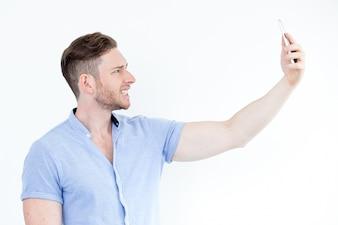 Ritratto di giovane uomo grimacing e prendere selfie