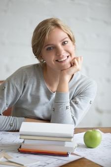 Ritratto di una giovane ragazza sorridente con libri e mela
