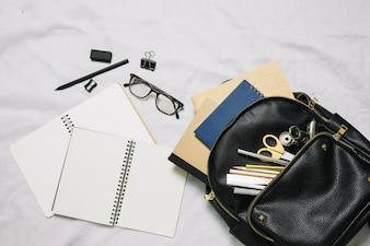 Schizzi vuoti e borsa con forniture per ufficio