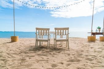 Sedie bianche e tavola sulla spiaggia