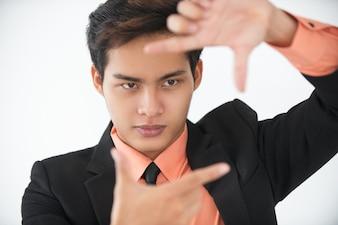 Serio giovane imprenditore mostrando cornice di dito
