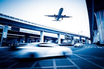 Sfocata scena di strada in città con un aereo che vola sopra