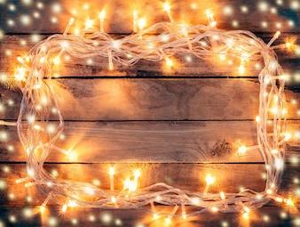 Sfondo di decorazione natalizia - vintage legno planato con luci e neve con testo di copia spazio.