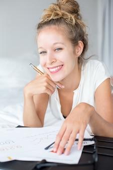 Signora sorridente di affari che lavora con il documento sul letto